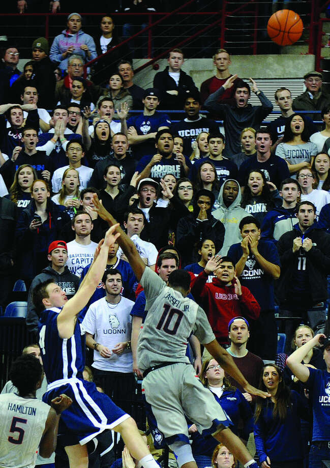 Yale's Jack Montague (4) shoots a game winning three-point shot while being guarded by Connecticut's Sam Cassell Jr. (10) during the second half of Yale's 45-44 upset victory in an NCAA college basketball game in Storrs, Conn., on Sunday, Dec. 5, 2014. (AP Photo/Fred Beckham)