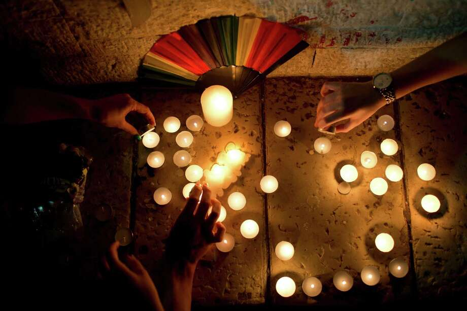 Members of the LGBT community light candles in solidarity with Florida's shooting attack victims, in Tel Aviv, Israel, Sunday, June 12, 2016.  The shooting attack in Orlando, Florida, USA, Sunday, left more than 50 people dead amid a multitude of events celebrating LGBT Pride Month. (AP Photo/Oded Balilty) Photo: Oded Balilty, STF / AP