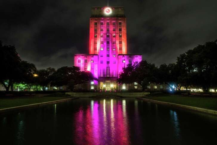 City Hall is lit up in multiple colors to honor the victims of the mass shooting in Orlando, Fla., on Sunday, June 12, 2016, in Houston.