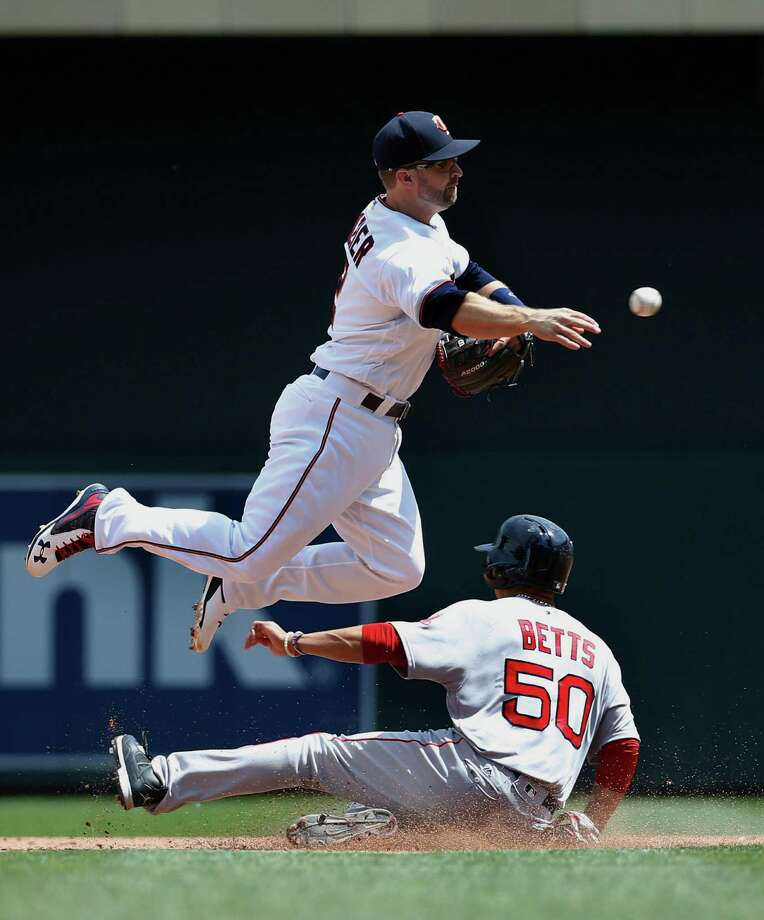 Minnesota Twins second baseman Brian Dozier, top, forces out Boston Red Sox's Mookie Betts (50) at second while jumping to turn a double play during the sixth inning of a baseball game in Minneapolis, Sunday, June 12, 2016. The Red Sox's Dustin Pedroia was out at first base. The Twins won 7-4. (AP Photo/Ann Heisenfelt) ORG XMIT: MNAH114 Photo: Ann Heisenfelt / FR13069 AP