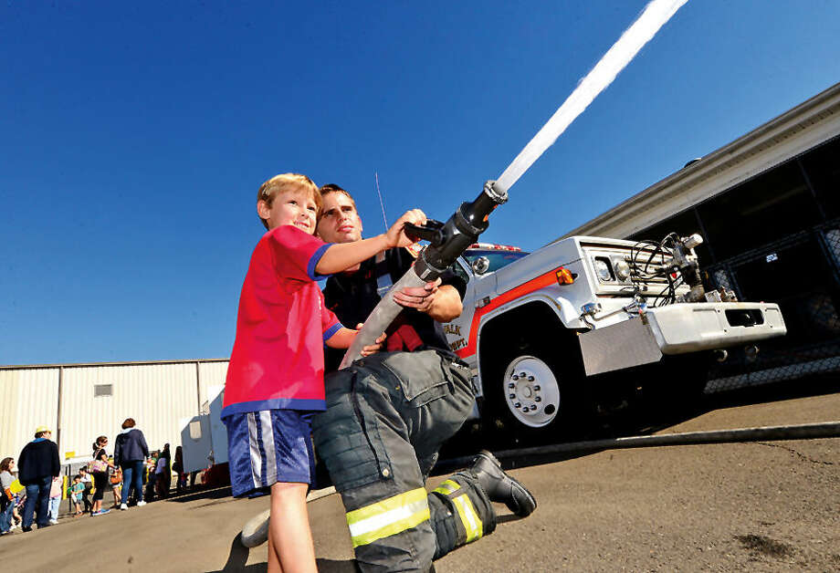 Hour photo / Erik Trautmann The Norwalk Fire, Police and Public Works Departments' Open House and Touch- a- Truck on Saturday at the Public Works Center on South Smith Street. All three Departments will featured hands-on activities, give-aways and demonstrations for all ages.