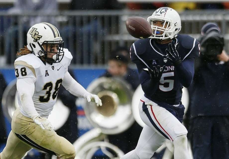 Connecticut wide receiver Noel Thomas (5) makes a touchdown reception in front of Central Florida defensive back Jordan Ozerities (38) during the second quarter of an NCAA college football game in East Hartford, Conn., Saturday, Nov. 1, 2014. (AP Photo/Michael Dwyer)