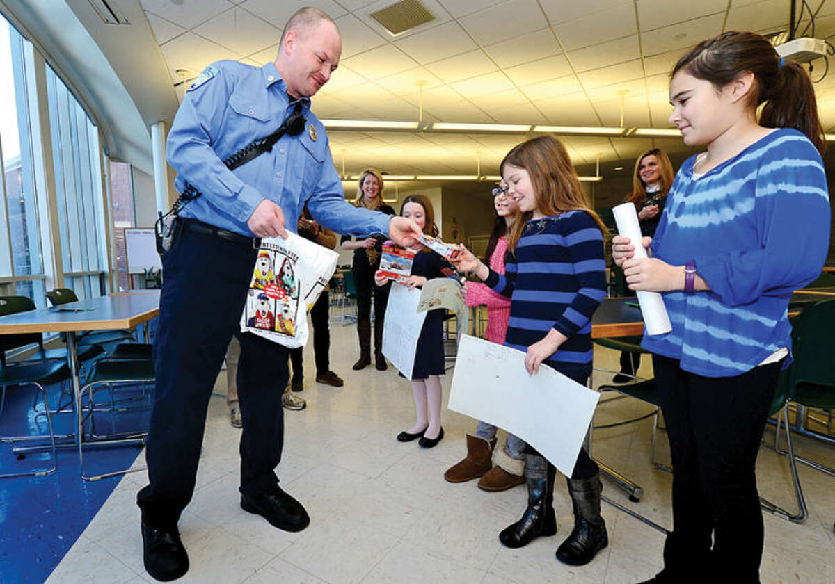 Hour photo / Erik Trautmann Cider Mill Elementary School 4th grader and Ella Donovan, 4th grader Tamar Rozenberg, 4th grader Grace Williams, and 5th grader Isabelle Braten receive winning recognition in the CT Fire Prevention Poster Contest awarded by Wilton Fire Department firefighter Dan Lewis and the Wilton Firefighters Local 2233 Thursday at the school.