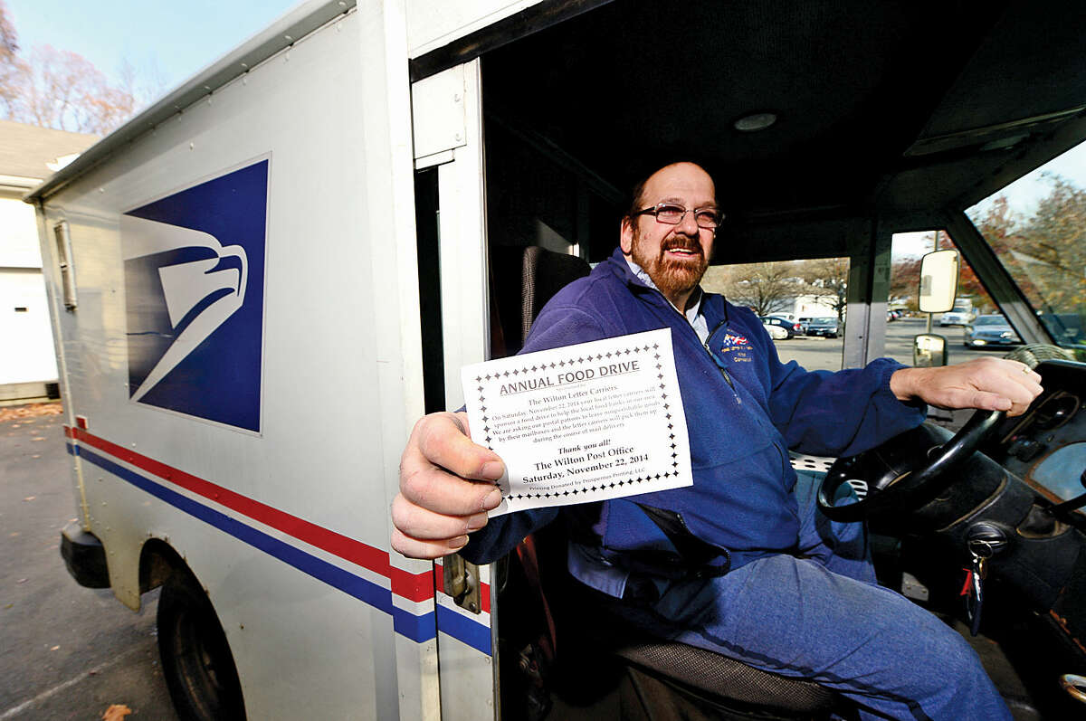 Postal worker Alan Horowitz displays the card advertising the postal carriers food drive for needy families on Thanksgiving. The carriers will pick up non-perishable food items at mailboxes.