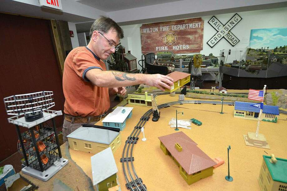 Richard Fuhrman places a ranch house from the 1950s into the Great Trains exhibit at the Wilton Historical Society.