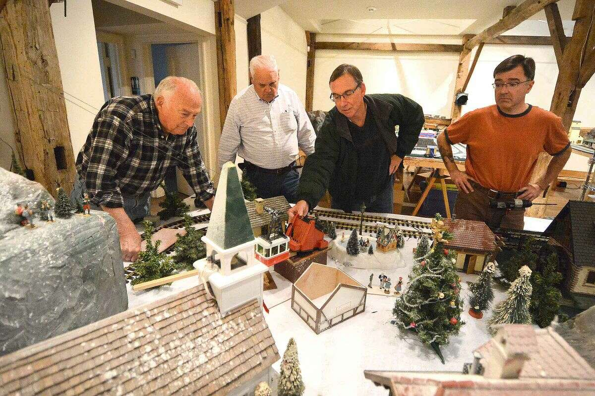 Ivan Spangenberg, Martin Hammer, Paul Lourd and Richard Fuhrman get the cable car to run smoothly as they work on the Great Trains display at he Wilton Historical Society.