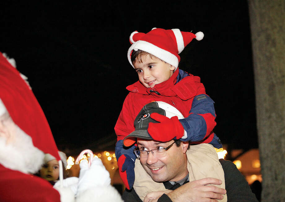 liver Richards receives a candy cane from Santa while sitting on his father, Ray Richard's, shoulders during the annual Wilton tree lighting and Holiday Stroll.