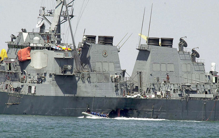 FILE -- This Sunday Oct. 15, 2000 file photo shows investigators in a speed boat examining the hull of the USS Cole at the Yemeni port of Aden, after a powerful explosion ripped a hole in the U.S Navy destroyer. Jurors should know how the government plans to execute the Guantanamo detainee accused of orchestrating the 2000 bombing of the USS Cole if he's convicted of a capital offense, his lawyer argued at a pretrial hearing Tuesday at the U.S. naval base in Cuba. Prosecutors countered that any execution method specified before the trial of Abd al Rahim al-Nashiri could be changed during the lengthy appeals process that would follow his sentencing, so jurors don't need to know. (AP Photo/Dimitri Messinis, File)