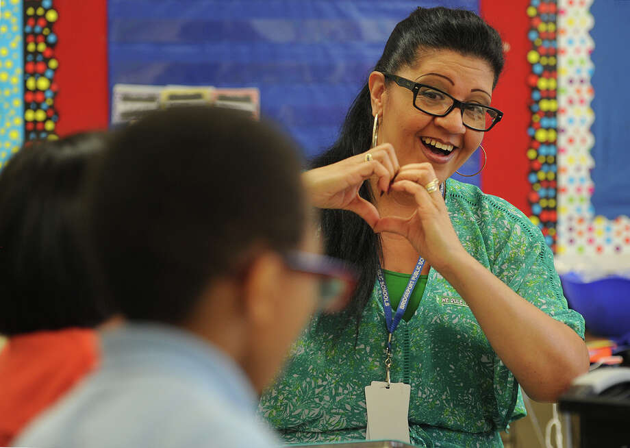 """Teaching assistant Margie Perez makes a heart """"love"""" sign to one of the students in a kindergarten classroom at Blackham School in Bridgeport. Teaching assistants' jobs are on the Board of Education chopping block as it faces a huge budget shortfall next year. Photo: Brian A. Pounds / Hearst Connecticut Media / Connecticut Post"""
