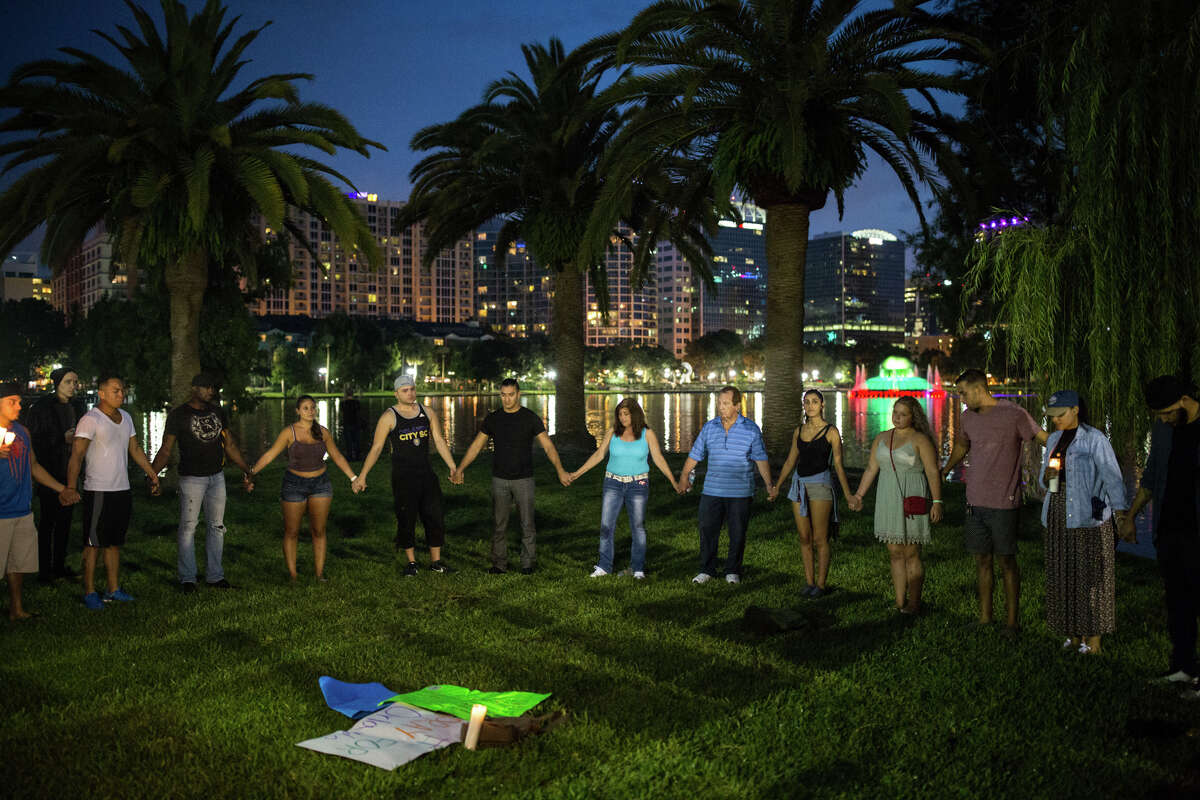 Mourners gather at a candlelight vigil at Lake Eola Park in downtown Orlando, Fla., to honor the victims of a mass shooting on Sunday, June 12, 2016. The shooting took place in the early morning hours of Sunday, June 12, at an Orlando nightclub called Pulse.
