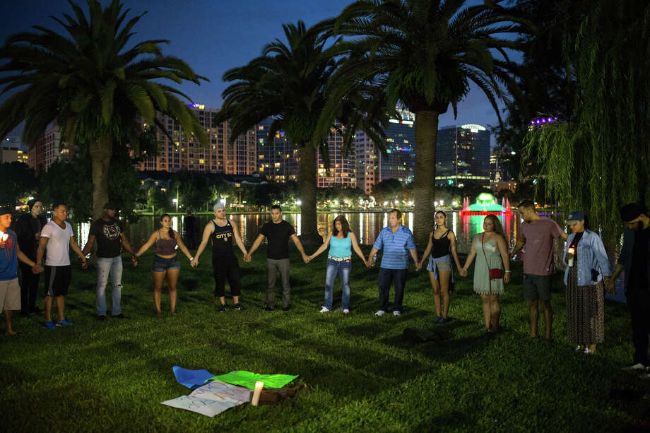 Mourners gather at a candlelight vigil at Lake Eola Park in downtown Orlando, Fla., to honor the victims of a mass shooting on Sunday, June 12, 2016. The shooting took place in the early morning hours of Sunday, June 12, at an Orlando nightclub called Pulse.  Photo: Loren Elliott, Associated Press / Tampa Bay Times