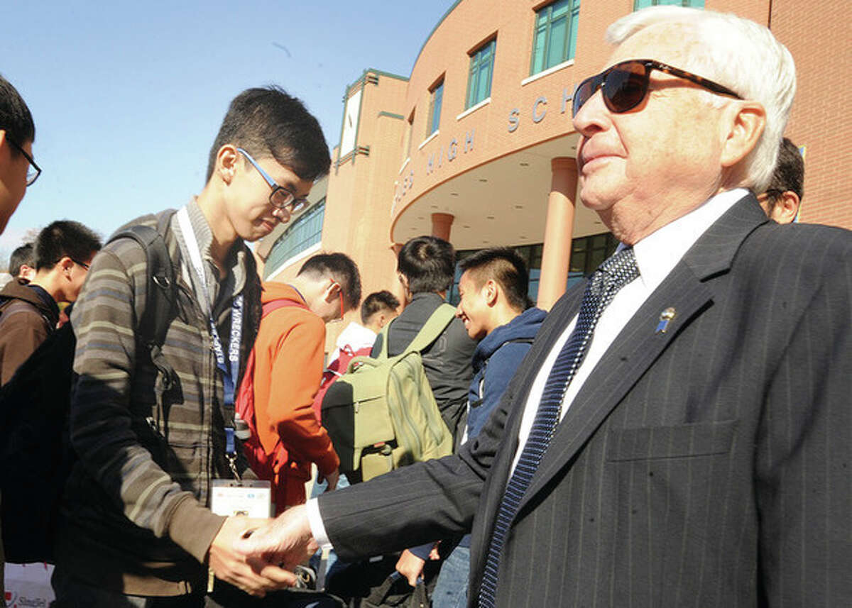 Superintendent of schools Elliott Landon greets Chinese student Zhou Zhefang as he steps off the bus at Staples High School Sunday in Westport. Hour photo/Matthew Vinci