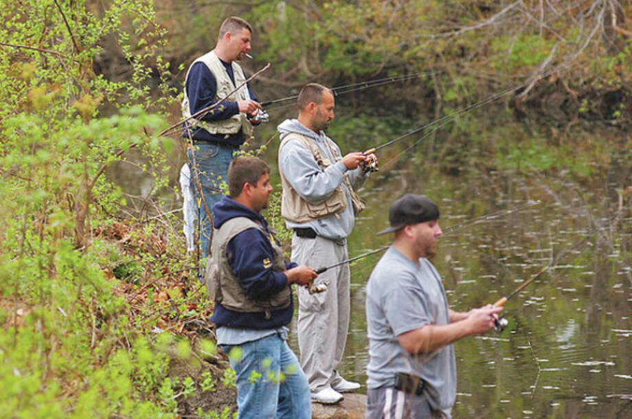 Above left: Kevin Botelho, Billy Montiro, Aderito Siera and Stephen Vieira fish on the Norwalk River in Wilton on opening day of trout season Saturday. Above right, Zach Liston, 11, also fishes on the Norwalk River on Saturday. / (C)2011, The Hour Newspapers, all rights reserved
