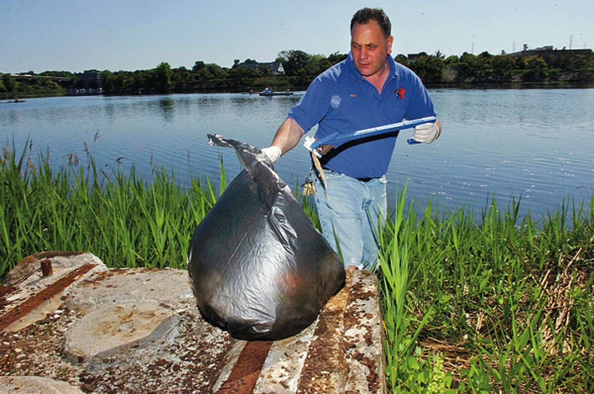 Mike Nuzzo helps Norwalk River Watershed Association and Norwalk Land Trust Clean Up at Heritage Park Saturday. Hour photo / Erik Trautmann