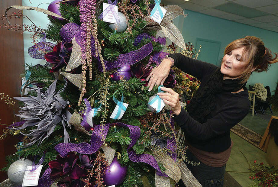 Danna DiElsi Owner of The Silk Touch places a tag on the Giving Tree at her Main Street boutique.