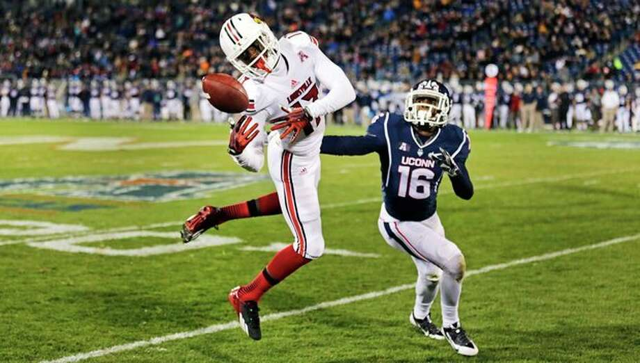 Louisville wide receiver James Quick (17) attempts to get a grip on the ball as Connecticut's Byron Jones (16) defends during the first half of an NCAA college football game, in East Hartford, Conn., Friday, Nov. 8, 2013. (AP Photo/Charles Krupa) / AP