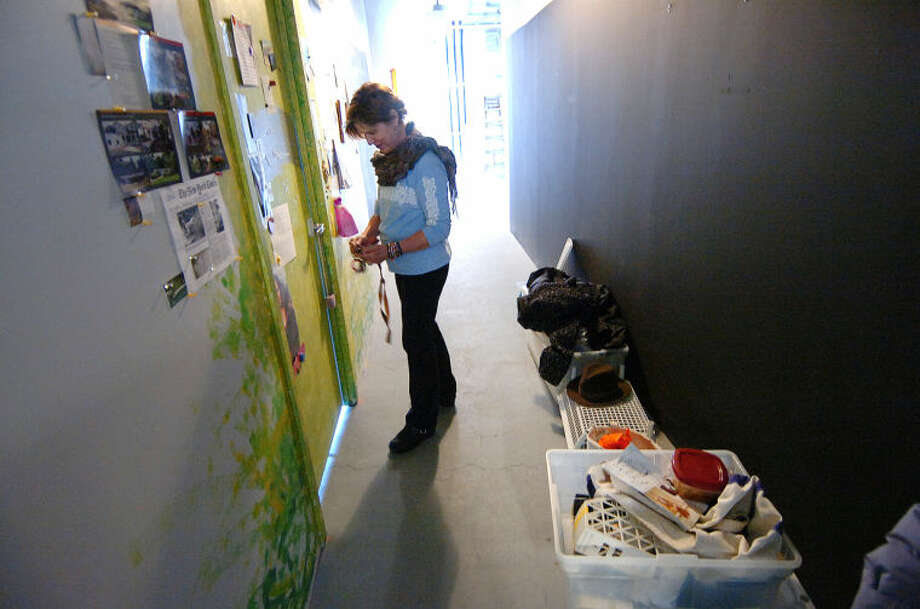 Artist Wendi Ohlson unlocks the door to her studio of five years, while items have been placed in the hallway as she organizes and packs for a potential move from the Loft Artist Association Studios and Gallery in Stamford.