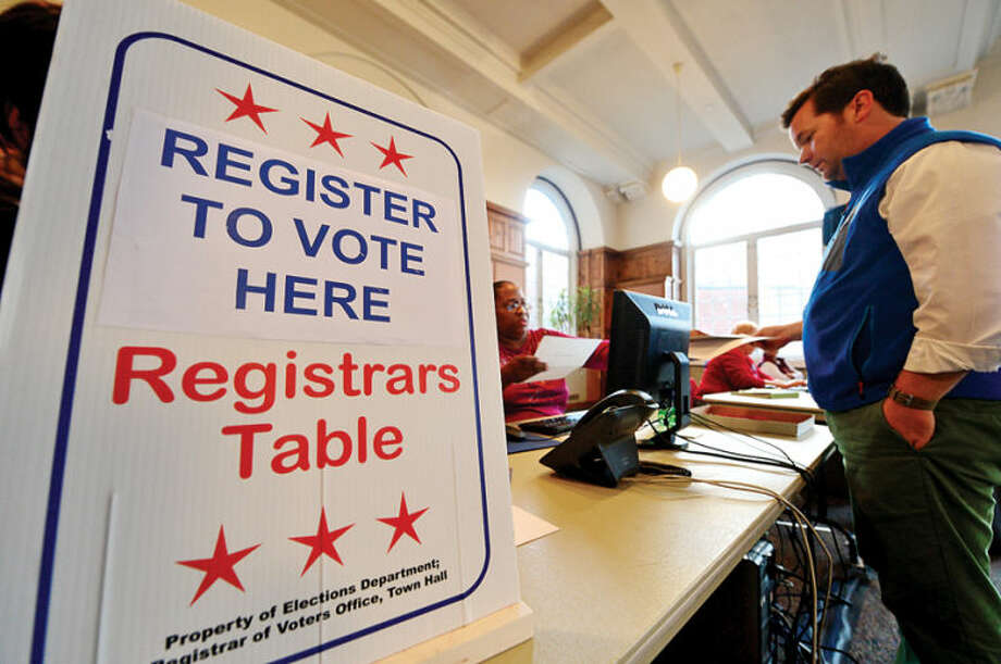 Hour photo / Erik Trautmann Bill Merz registers to vote in the City Hall Community Room Tuesday. This is the first year Norwalk has same day voter registration.