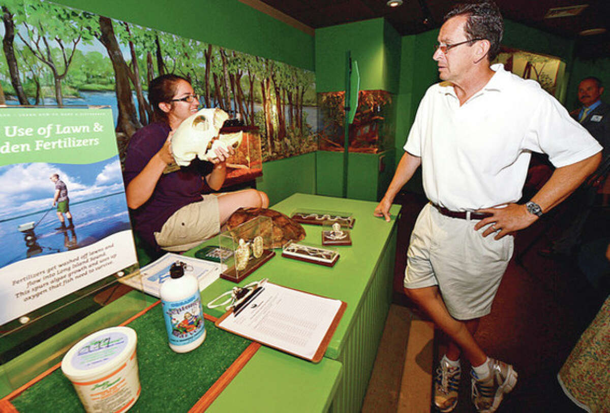 Gov. Dannel Malloy chats with an unidentified staff member at the Maritime Aquarium in Norwalk on Tuesday.