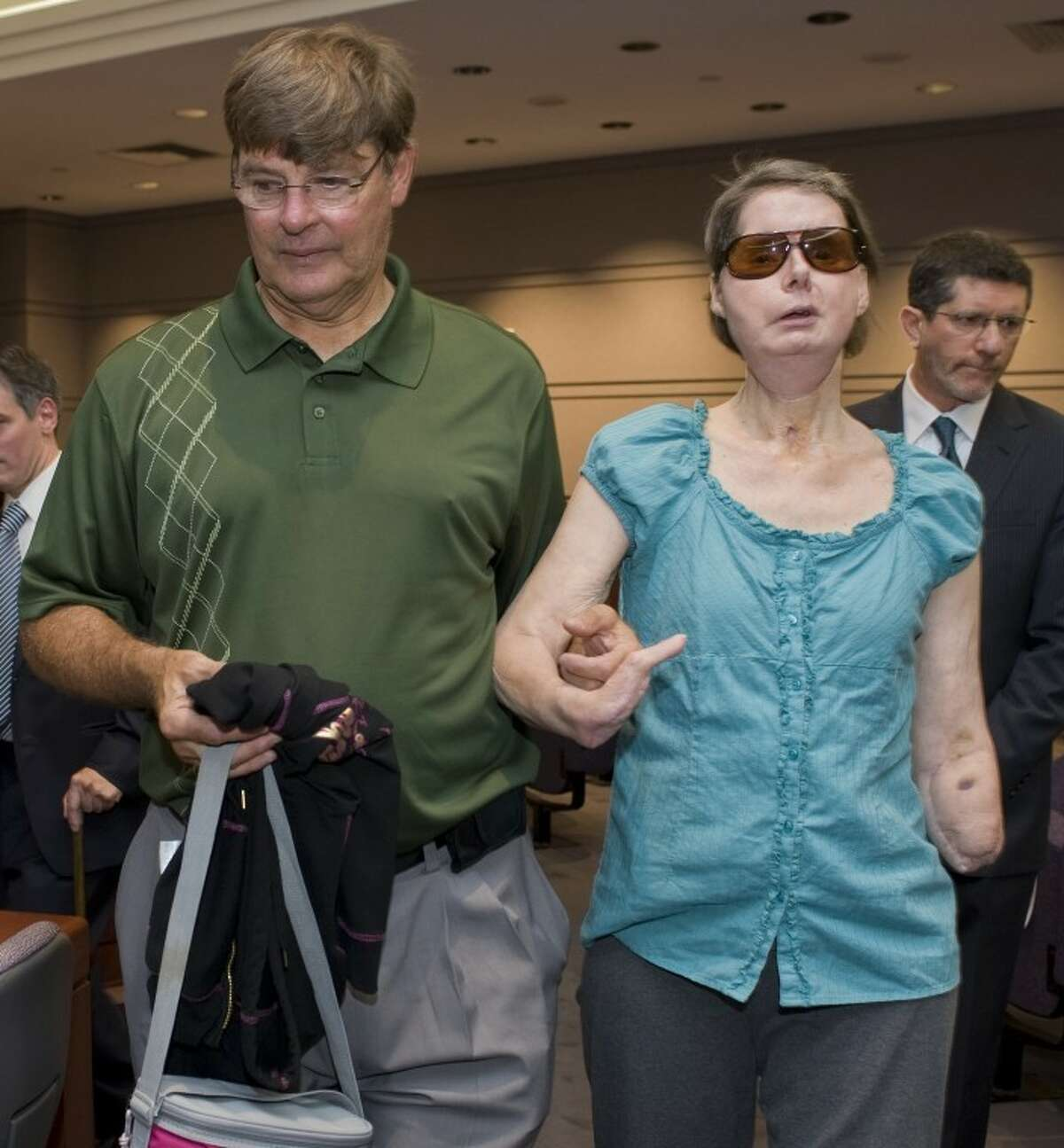 Charla Nash arrives with her brother Stephen, left, for a hearing at the Legislative Office Building in Hartford, Conn., Friday, Aug. 10, 2012. Nash who was mauled in a 2009 chimpanzee attack is attending a hearing to determine whether she may sue the state for $150 million in claimed damages. (AP Photo/Jessica Hill)