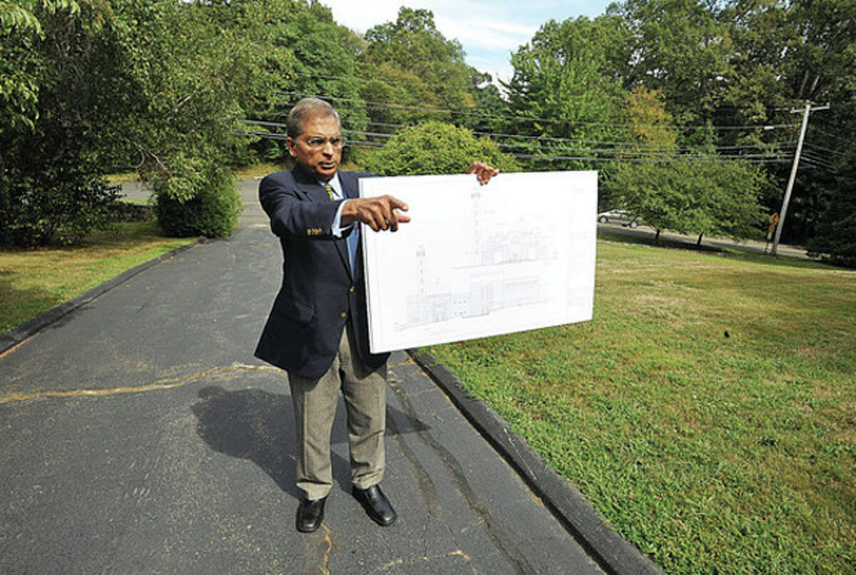 Architect Syed Ali points out where the 80 ft. minaret will be in his plans to build a mosque for the Al-Madany Islamic Center at 127 Fillow St. Hour photo / Erik Trautmann
