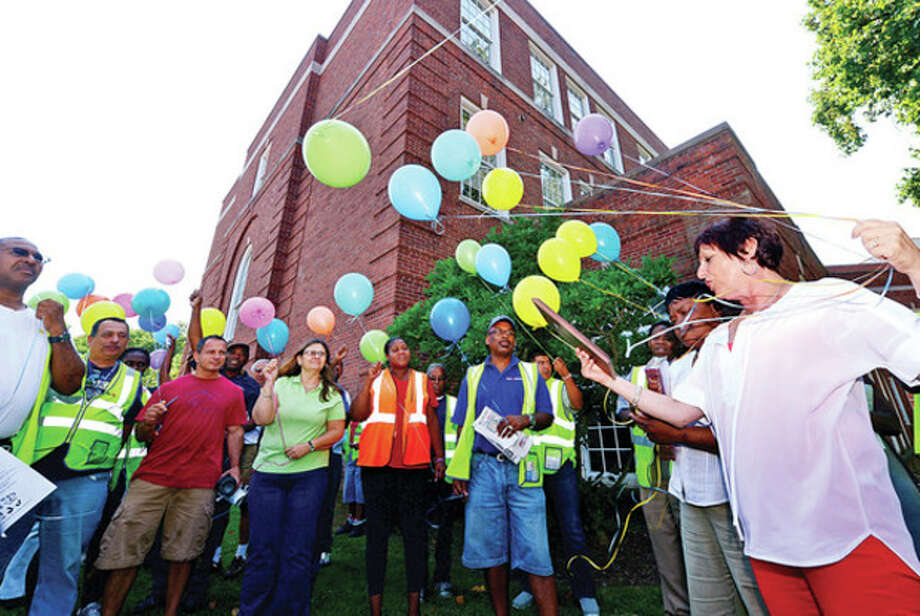 Hour photo / Erik TrautmannFirst Student location manager Theresa Taylor reads a plaque dedicated to Jesse Montgomery as the bus company and the Norwalk Public Schools Transportation Office honor the late bus driver, a long-time, well-loved employee by retiring his bus number and releasing balloons following the company's Start Up meeting Tuesday morning. / (C)2013, The Hour Newspapers, all rights reserved