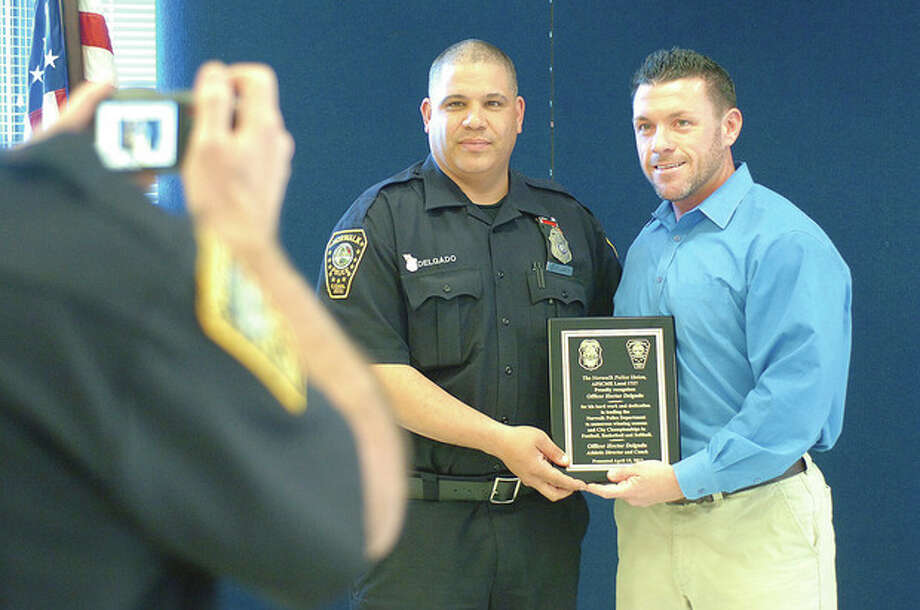 Hour Photo/Alex von Kleydorff Detectice Dave Orr, President of the union presents a plaque to Officer Hector Delgado for his involment with the Departments athletics / 2013 The Hour Newspapers