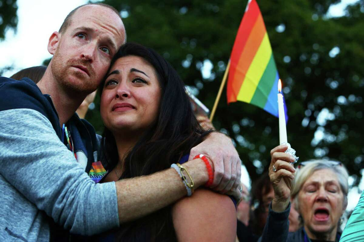 Jeffrey Erikson and Jamie Fernandez hold each other during a moment of silence at a vigil in Cal Anderson Park for the victims of a mass shooting at Pulse nightclub in Orlando, which killed 49 people and left 53 more injured, Sunday, June 12, 2016.