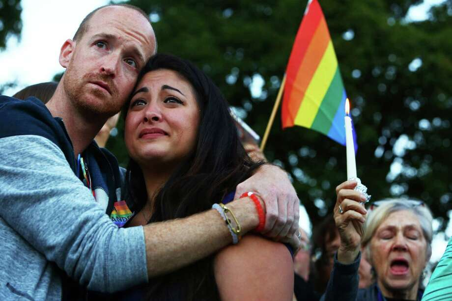 Jeffrey Erikson and Jamie Fernandez hold each other during a moment of silence at a vigil in Cal Anderson Park for the victims of a mass shooting at Pulse nightclub in Orlando, which killed 49 people and left 53 more injured, Sunday, June 12, 2016. Photo: GENNA MARTIN,  SEATTLEPI.COM STAFF / SEATTLEPI.COM