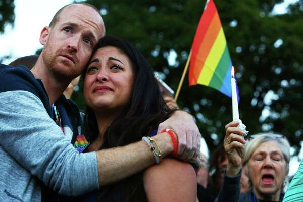 Jeffrey Erikson and Jamie Fernandez hold each other during a moment of silence at a vigil in Cal Anderson Park for the victims of a mass shooting at Pulse nightclub in Orlando, which killed 50 people and left 53 more injured, Sunday, June 12, 2016.