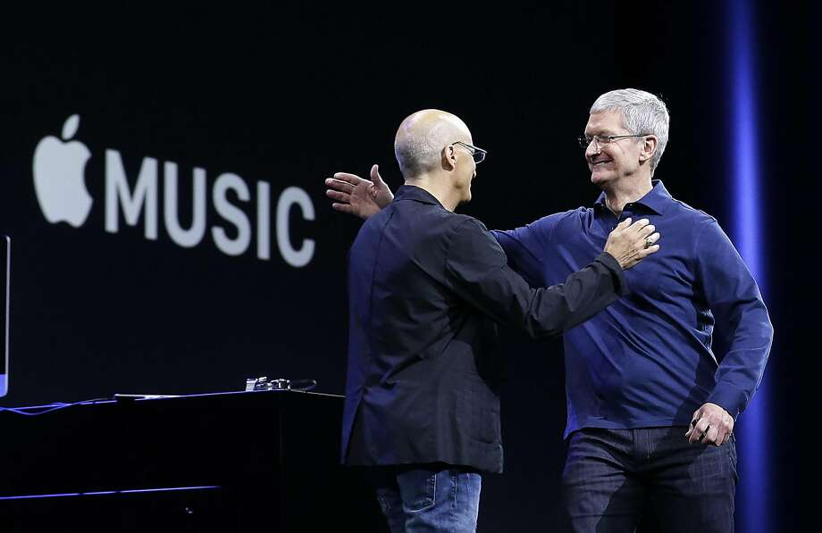 Apple CEO Tim Cook, right, hugs Beats by Dre co-founder and Apple employee Jimmy Iovine at the Apple Worldwide Developers Conference in San Francisco, Monday, June 8, 2015. The maker of iPods and iPhones announced Apple Music, its new, paid streaming-music service at the 2015 conference. (AP Photo/Jeff Chiu) Photo: Jeff Chiu, Associated Press
