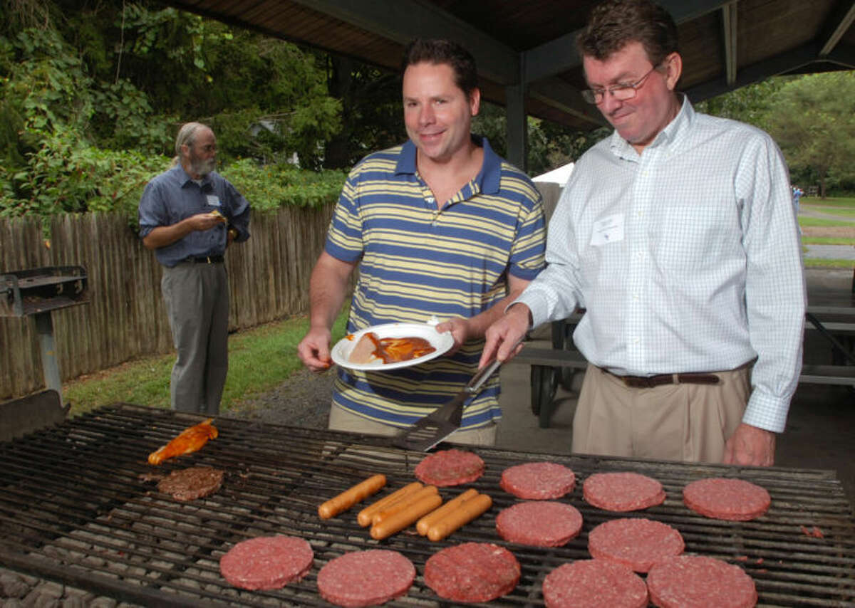 Richard Creeth and Ted Hoffstatter tend the grill during the Democratic Town Committee annual picnic at Merwin Meadows in this September 2009 file photo.