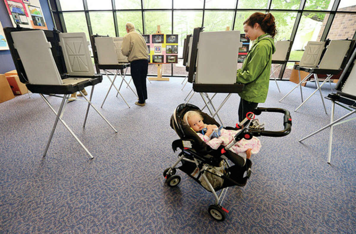 Hour photo / Erik Trautmann Wilton residents, including Sarah Santisi, who brought along her daughter Kaitlyn, 20 months, to vote on the municipal, education budgets and capital projects Saturday at Wilton High School.