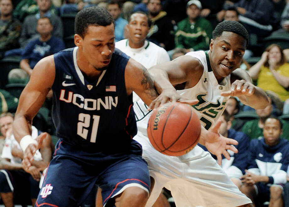 CORRECTS SOUTH FLORIDA PLAYER TO ZACH DELAY, INSTEAD OF JAVONTAE HAWKINS - South Florida's Zach LeDay, right, and Connecticut guard Omar Calhoun (21) tangle for control of the ball during the first half of an NCAA college basketball game Wednesday, March 6, 2013, in Tampa, Fla. (AP Photo/The Tampa Tribune, Chris Urso) ST. PETE, LAKELAND, BRADENTON OUT , MAGS OUT LOCAL TV OUT: WTSP CH 10, WFTS CH 28, WTVT CH 13, BAYNEWS 9 / The Tampa Tribune