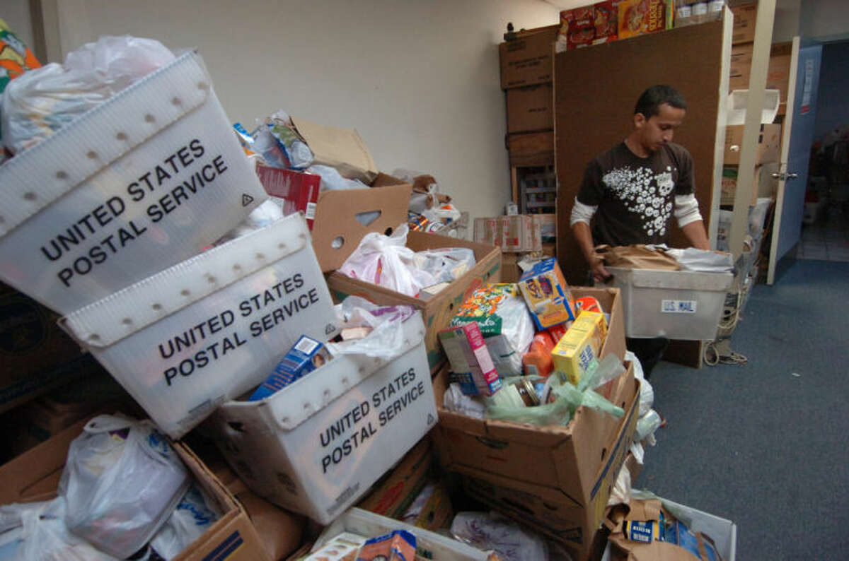 Raf Santaella, art director with Integrated Marketing Services in Norwalk, helps with sorting donated food from the Wilton Post Office food drive in this file photo.