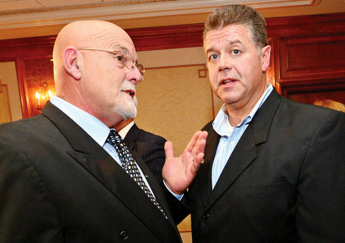 Hour photo / Erik Trautmann Jerry Petrini and Artie Kassimis confer during election night at the Norwalk Inn Tuesday.