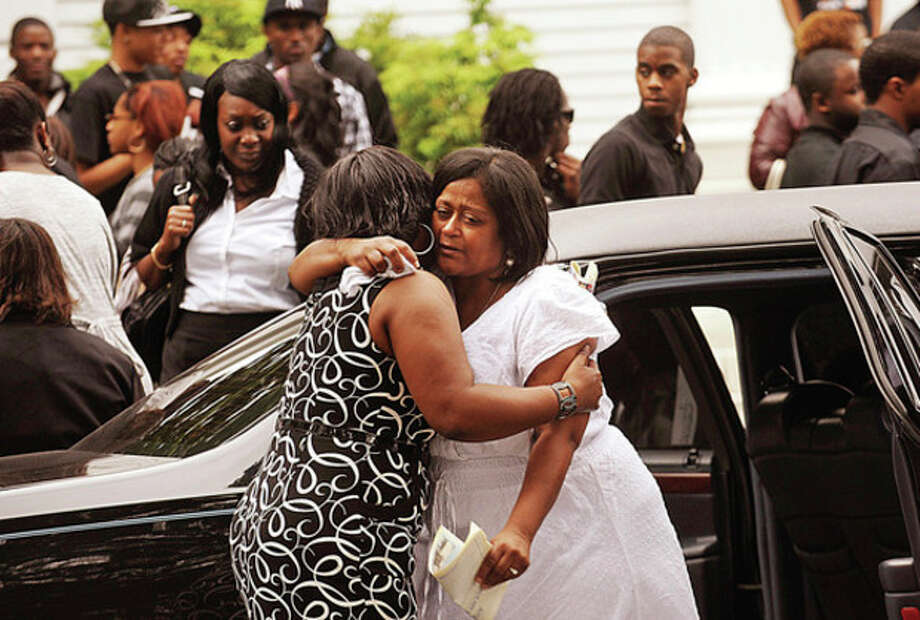 Sandra Stephenson comforts the mother of Amos Brown Jr., Shannon Roberts, following the funeral service at the First Congregational Church on the Green Tuesday morning. / (C)2010 The Hour