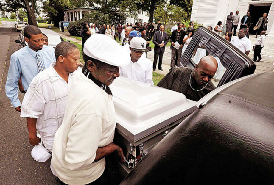 Pallbearers take the body of Amos Brown Jr. for burial following the funeral service at the First Congregational Church on the Green Tuesday morning. / (C)2010 The Hour