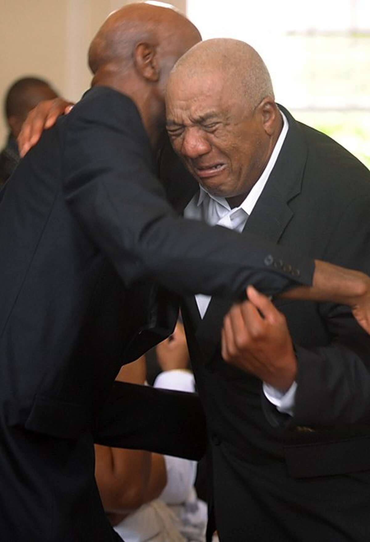John Mosby grieves with good friend Amos Brown Sr before the funeral service of Amos Brown Jr. at the First Congregational Church on the Green Tuesday morning. Hour photo / Erik Trautmann