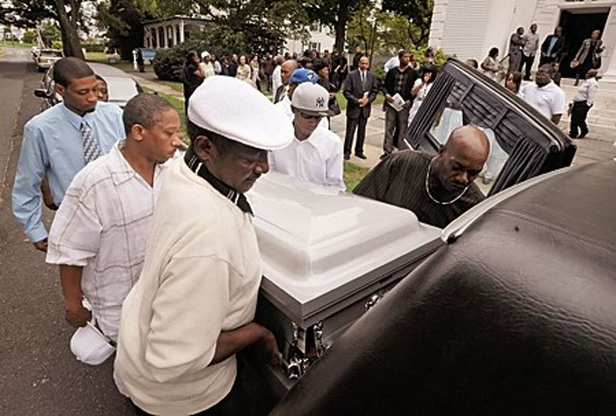 Pallbearers take the body of Amos Brown Jr. for burial following the funeral service at the First Congregational Church on the Green Tuesday morning. Hour photo / Erik Trautmann
