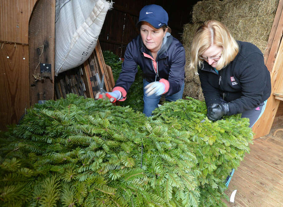Volunteers Sarah Boatwalla and Beth Culmane organize the different size wreaths in the hay barn for Friends of Ambler Farm's Annual Holiday Greens Sale.