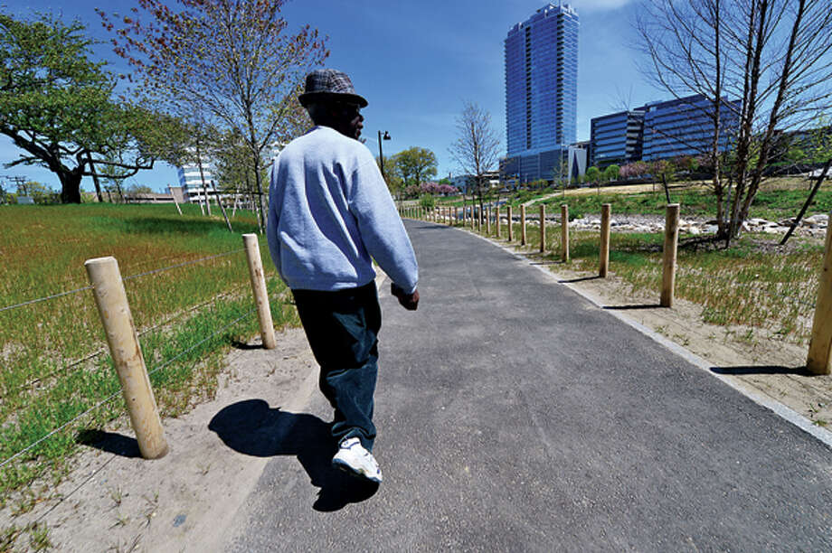 Local residents including Antoine Geffrard enjoy the newly opened Mill River Park in Stamford Tuesday. Hour photo / Erik Trautmann / (C)2013, The Hour Newspapers, all rights reserved