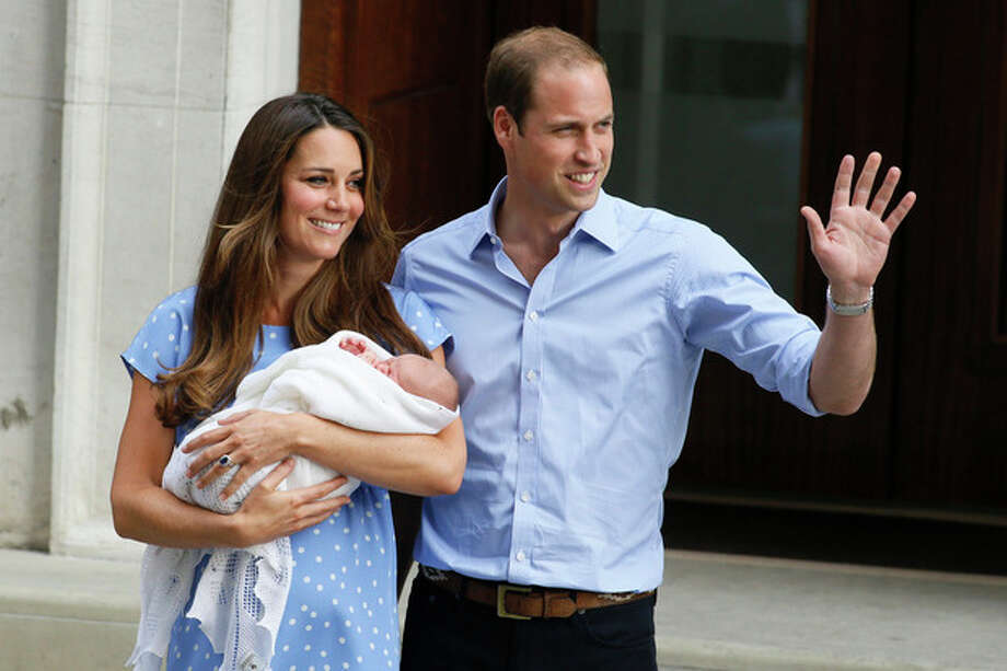Britain's Prince William, right, and Kate, Duchess of Cambridge, hold the Prince of Cambridge, Tuesday July 23, 2013, as they pose for photographers outside St. Mary's Hospital exclusive Lindo Wing in London where the Duchess gave birth on Monday July 22. The Royal couple are expected to head to London's Kensington Palace from the hospital with their newly born son, the third in line to the British throne. (AP Photo/Kirsty Wigglesworth) / AP