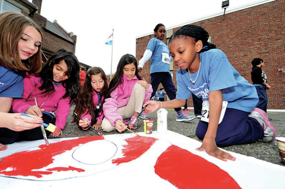 Hour photos / Erik TrautmannSide by Side Charter School 4th- and 5th-graders Laura weiss, Miranda Silva Meza, Cainav Khan, Kelsey Nava and Aaliyah Laport paint a banner after participating in the World Marathon Challenge, a fundraiser for Save the Children Wednesday. / (C)2013, The Hour Newspapers, all rights reserved