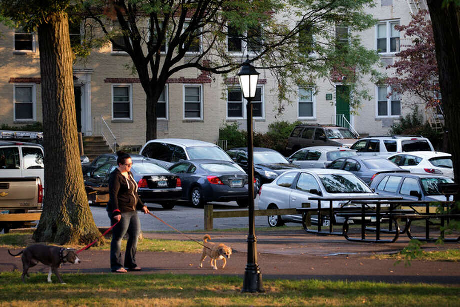 A dog-walker passes outside the apartment complex where Miriam Carey is believed to have lived in Stamford, Conn., Friday, Oct. 4, 2013. Law-enforcement authorities have identified Carey, 34, as the woman who, with a 1-year-old child in her car, led Secret Service and police on a harrowing chase in Washington from the White House past the Capitol Thursday, attempting to penetrate the security barriers at both national landmarks before she was shot to death, police said. The child avoided serious injury and was taken into protective custody. (AP Photo/John Minchillo) / FR170537 AP