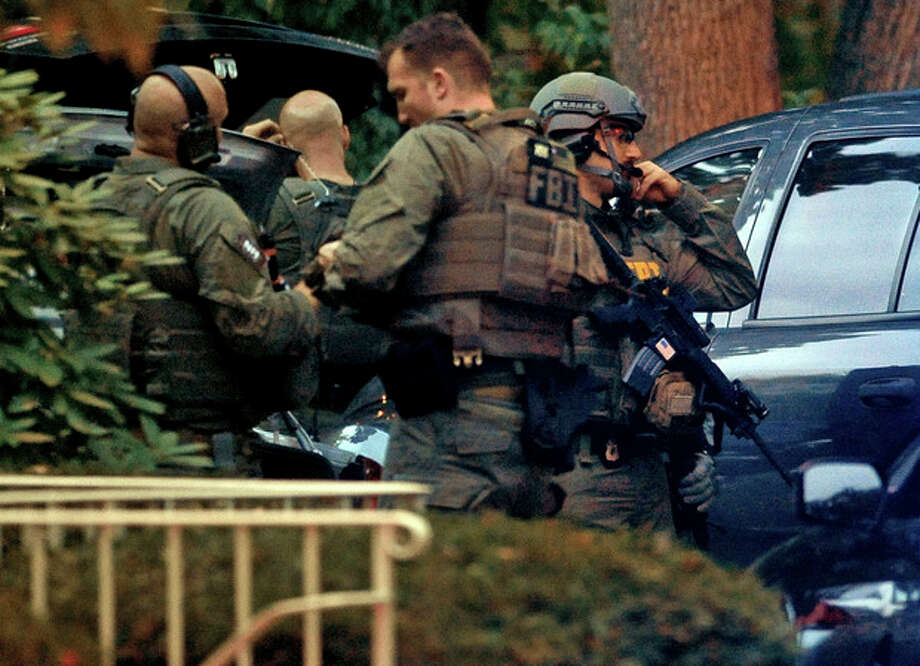 Members of the FBI suit up outside the residence of Miriam Carey in Stamford, Conn. Thursday, Oct. 3, 2013. Law-enforcement authorities have identified Carey, 34, as the woman who, with a 1-year-old child in her car, led Secret Service and police on a harrowing chase in Washington from the White House past the Capitol Thursday, attempting to penetrate the security barriers at both national landmarks before she was shot to death, police said. The child survived. (AP Photo/The Stamford Advocate, Christian Abraham) MANDATORY CREDIT / The Stamford Advocate