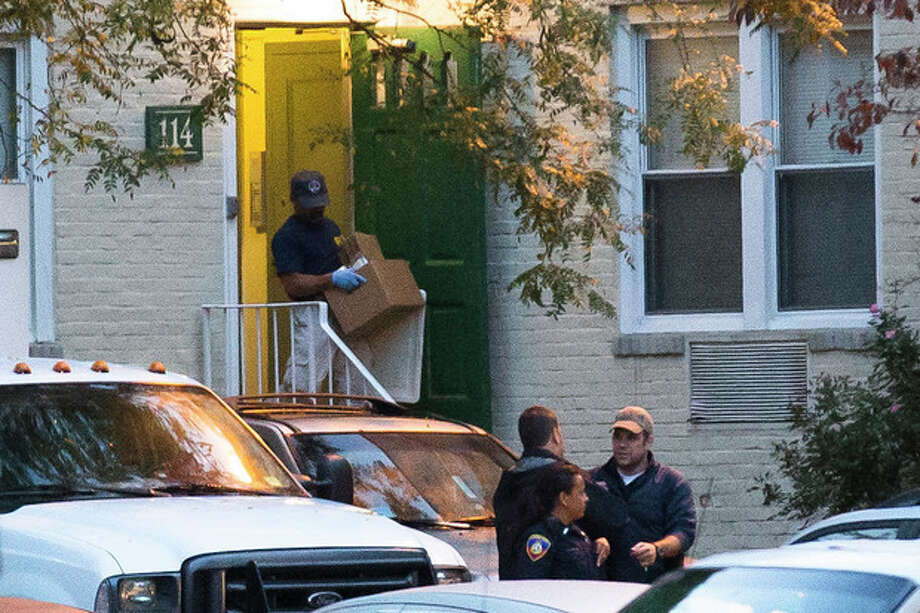 A federal agent removes evidence from the apartment complex where Miriam Carey is believed to have lived in Stamford, Conn., Friday, Oct. 4, 2013. Law-enforcement authorities have identified Carey, 34, as the woman who, with a 1-year-old child in her car, led Secret Service and police on a harrowing chase in Washington from the White House past the Capitol Thursday, attempting to penetrate the security barriers at both national landmarks before she was shot to death, police said. The child survived. (AP Photo/John Minchillo) / FR170537 AP