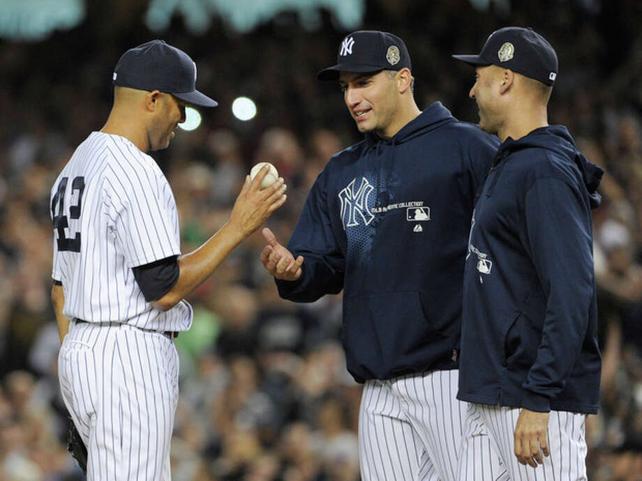 New York Yankees relief pitcher Mariano Rivera, left, hands the ball to Andy Pettitte as Derek Jeter, right, watches during the ninth inning of a baseball game against the Tampa Bay Rays on Thursday, Sept. 26, 2013, at Yankee Stadium in New York. The Yankees defeated the Rays 4-0 in Rivera's final home game with the team. (AP Photo/Bill Kostroun) / FR51951 AP