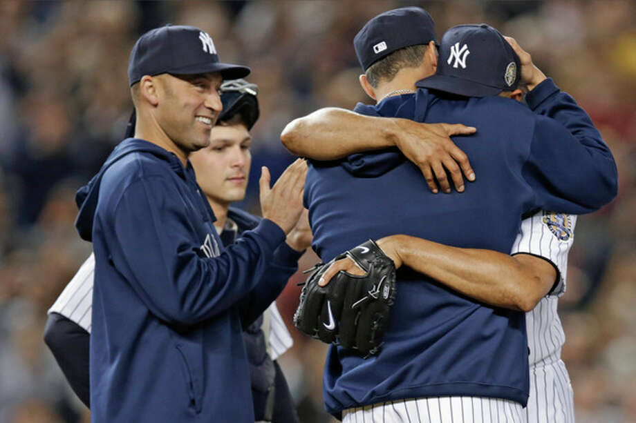 New York Yankees' Derek Jeter, left, applauds as retiring Yankees pitcher Andy Pettitte, back to camera, embraces relief pitcher Mariano Rivera in the ninth inning of Rivera's final appearance at a baseball game at Yankee Stadium, Thursday, Sept. 26, 2013, in New York. The Yankees defeated the Tampa Bay Rays 4-0. (AP Photo/Kathy Willens) / AP