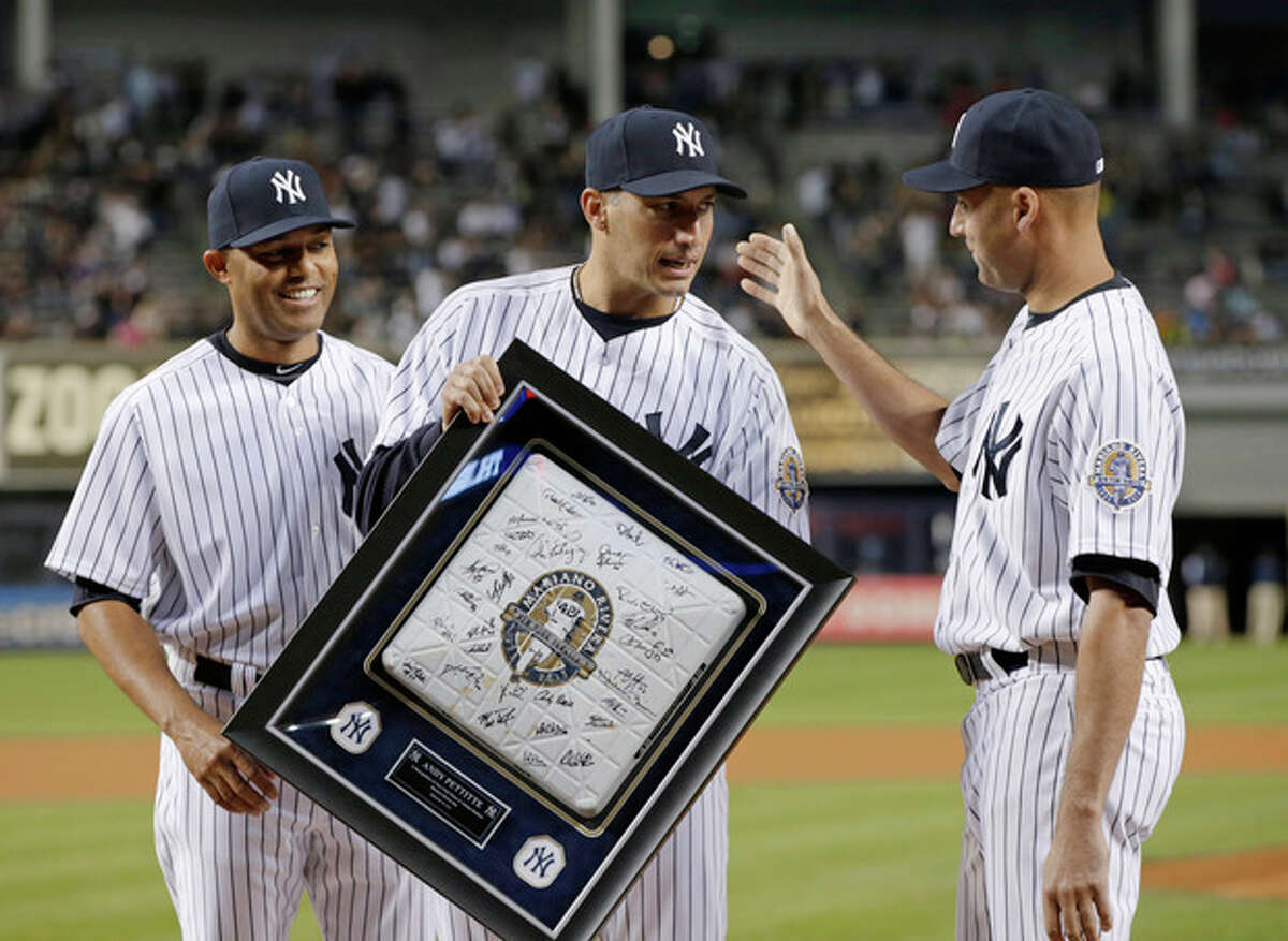 New York Yankees relief pitcher Mariano Rivera, left, and shortstop Derek Jeter, right. congratulate pitcher Andy Pettitte, who holds a base from his final game during a ceremony before the Yankees' baseball game against the Tampa Bay Rays, Wednesday, Sept. 25, 2013, in New York. (AP Photo/Kathy Willens)